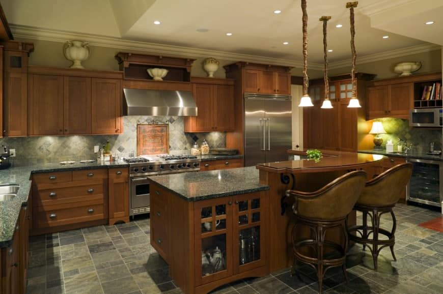 Brown kitchen featuring black granite countertops on kitchen counters. It has a breakfast bar lighted by pendant lights.