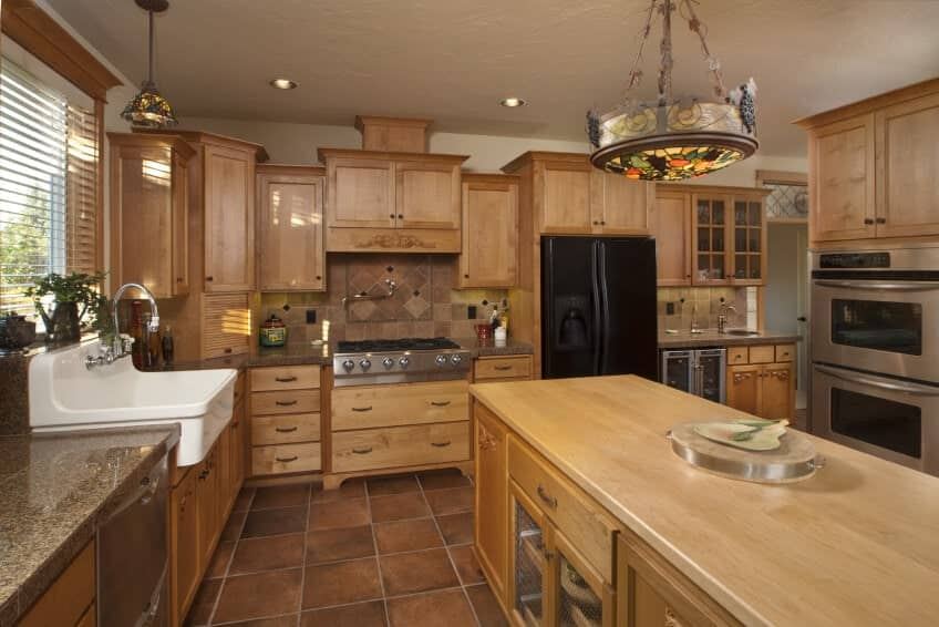 This kitchen boasts brown cabinetry, kitchen counters and center island along with brown tiles flooring.