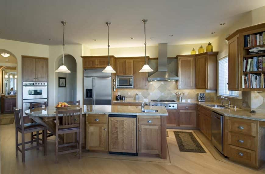 Spacious kitchen featuring space for a breakfast bar lighted by three pendant lights. The kitchen also features brown cabinetry and kitchen counters.
