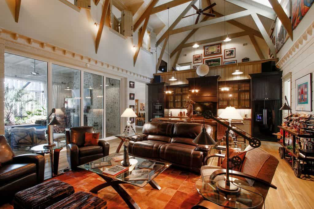 Large living room area featuring brown leather seats and a brown rug covering the hardwood flooring. The home also features a tall ceiling with exposed beams.