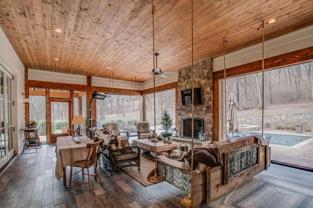 Large living space featuring hardwood flooring and a wooden ceiling. The room offers cozy seats and a fireplace with a TV on top of it.