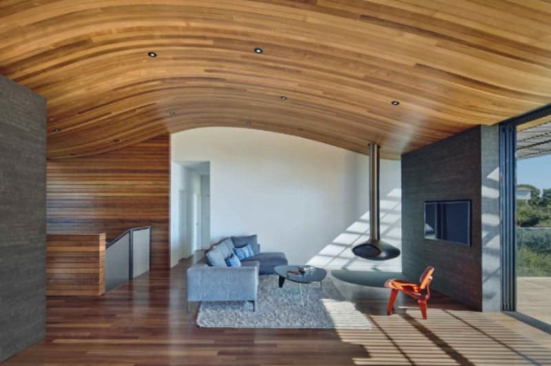 A large great room featuring a living space with a gray sofa set on top of an area rug. The ceiling of the home is very stylish and is made of wood.