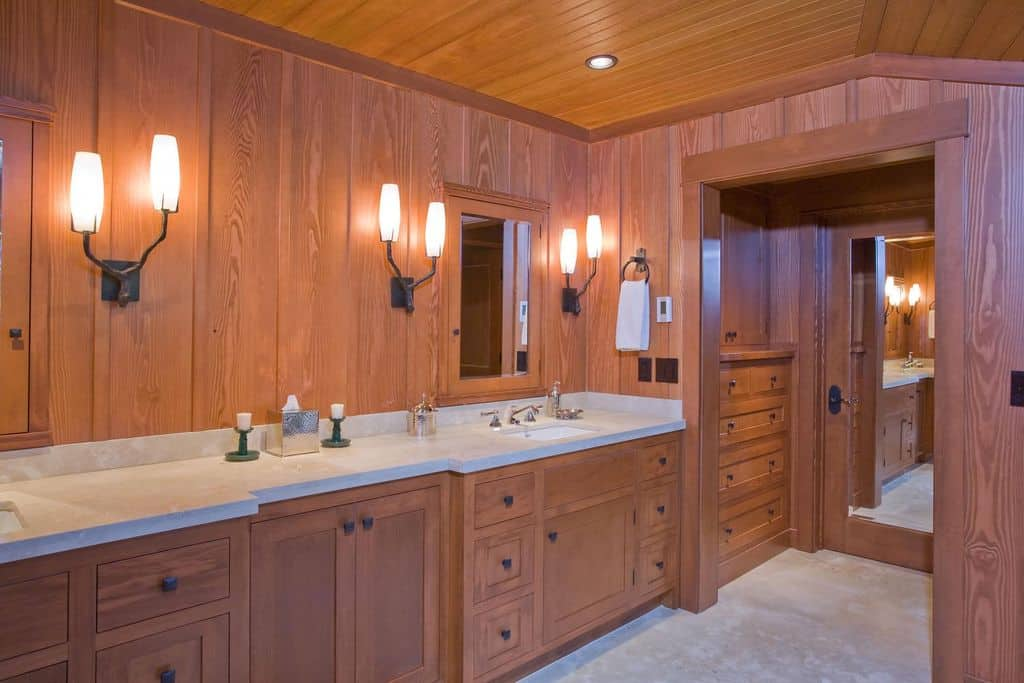 Brown primary bathroom featuring wooden walls and ceiling. It has a long sink counter with two sinks lighted by wall lighting.