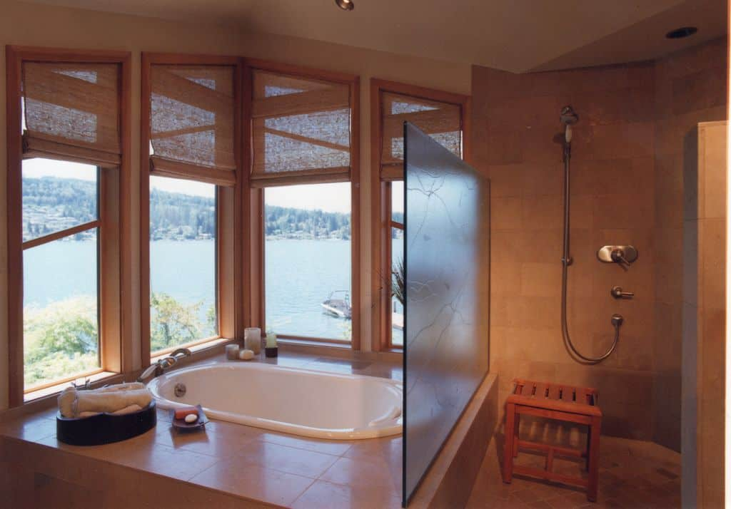 A brown kitchen with a drop-in tub and a walk-in shower room. The tub is situated near the glass windows overlooking the beautiful surroundings.