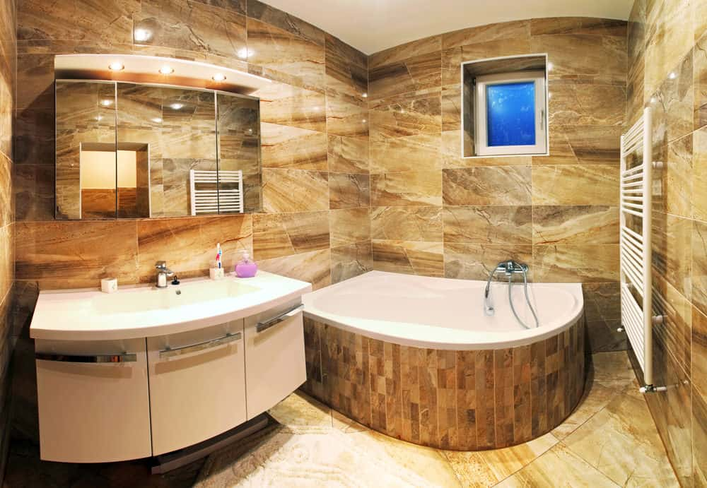 Small master bathroom featuring a modish sink counter and a corner tub surrounded by brown tiles walls and floors.