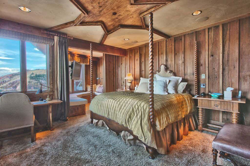 Brown master bedroom featuring its own living space along with a stylish ceiling design. The room also offers carpet flooring.