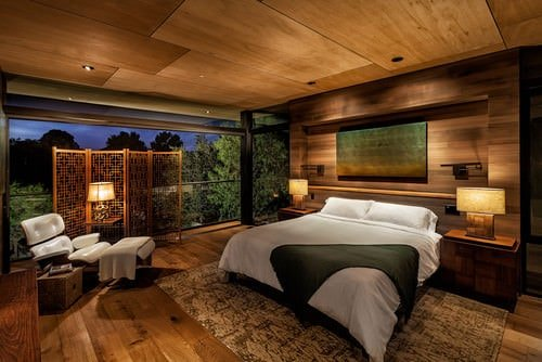Large brown master bedroom featuring a stylish wall and wooden ceiling matching the hardwood flooring.