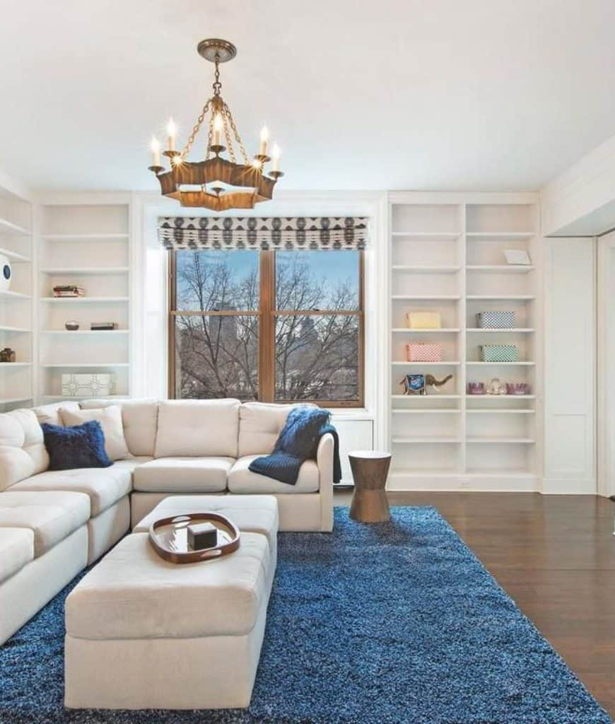 White living room accented with a blue shaggy rug and furry pillows that lay on the sectional sofa accompanied by a pair of ottomans. It has a marvelous chandelier and built-in shelving filled with various decors.