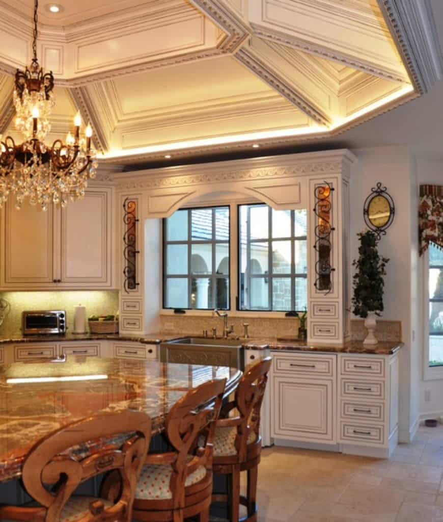 Elegant kitchen with limestone flooring and coffered tray ceiling mounted with a glam chandelier that hung over a marble top island bar lined by dotted cushioned stools.