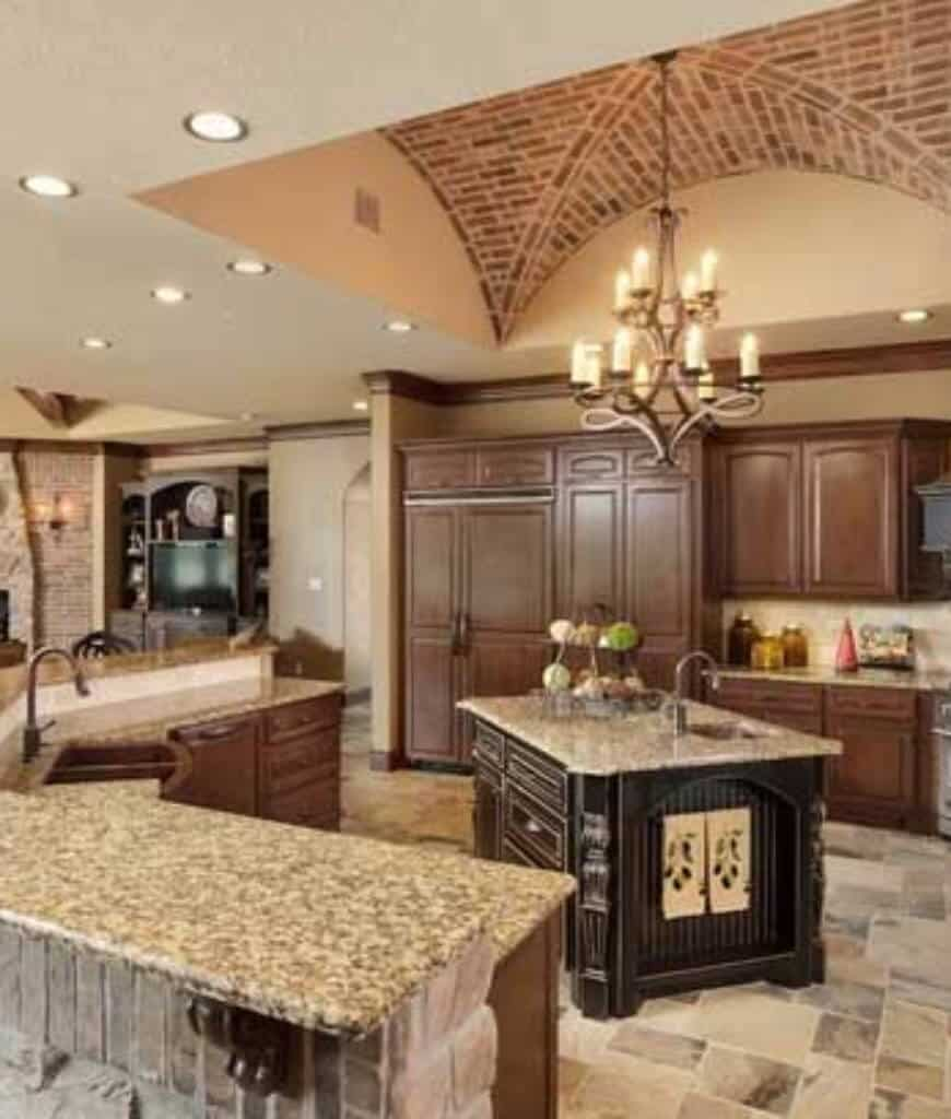 This kitchen is lighted by a two-tier candle chandelier that hangs over the black central island surrounded with wooden cabinetry and a curved island bar clad in stone bricks.