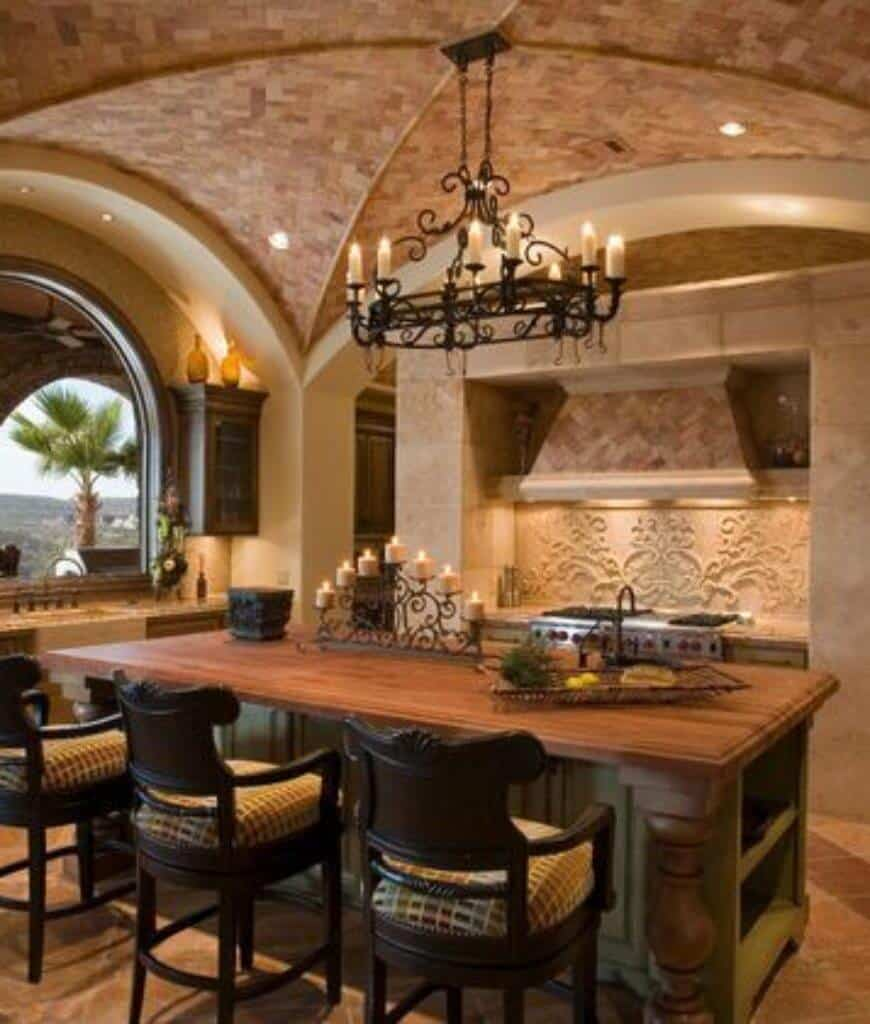 Mediterranean kitchen with chevron range hood fixed above the ornate backsplash and a wooden breakfast island lined with cushioned counter chairs and lighted by an oval-shaped chandelier.