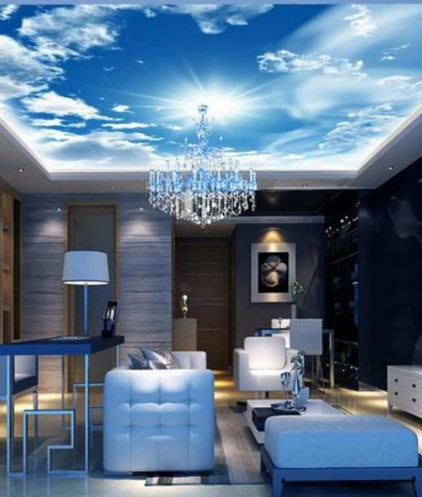 Magnificient living room boasts sleek white seats and a stunning tray ceiling with a sky mural. It is lighted by a crystal chandelier and table lamp that sits on a metal console table.