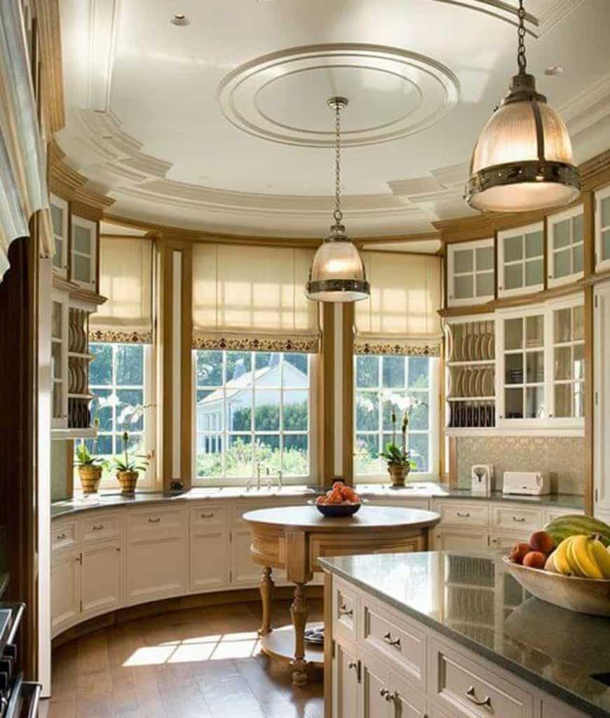 Country kitchen showcases a round wooden table that sits in between white cabinetry and matching breakfast bar lighted by glass dome pendants. It has wood plank flooring and white framed windows covered with lovely roman shades.