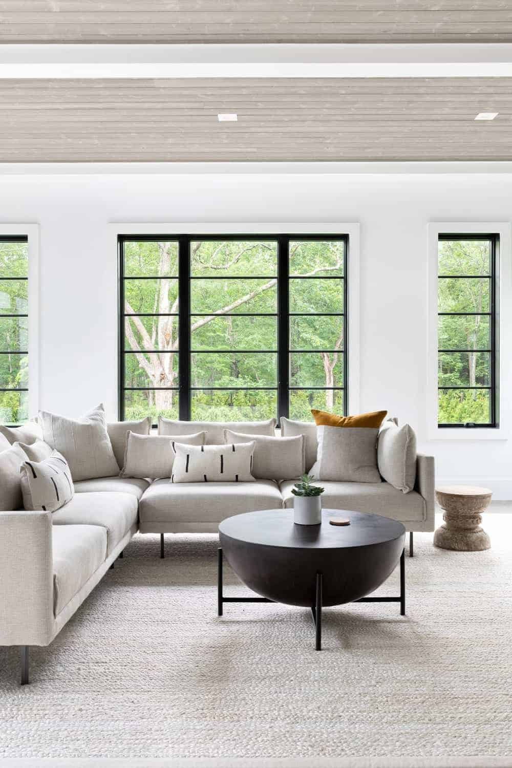 A focused look at this living room's L-shape modern sofa set on top of the large white area rug.
