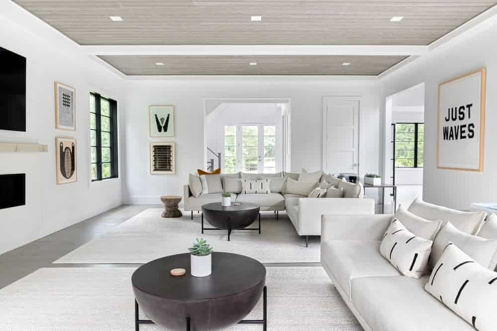 Large living room featuring white walls and dark hardwood floors topped by large white area rugs. There's a widescreen TV on the wall as well.