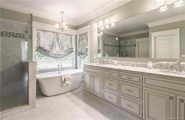 The primary bathroom has a freestanding porcelain bathtub at the far end under the window and topped with a simple chandelier. Beside this is the large wooden vanity paired with a wide wall-mounted mirror.