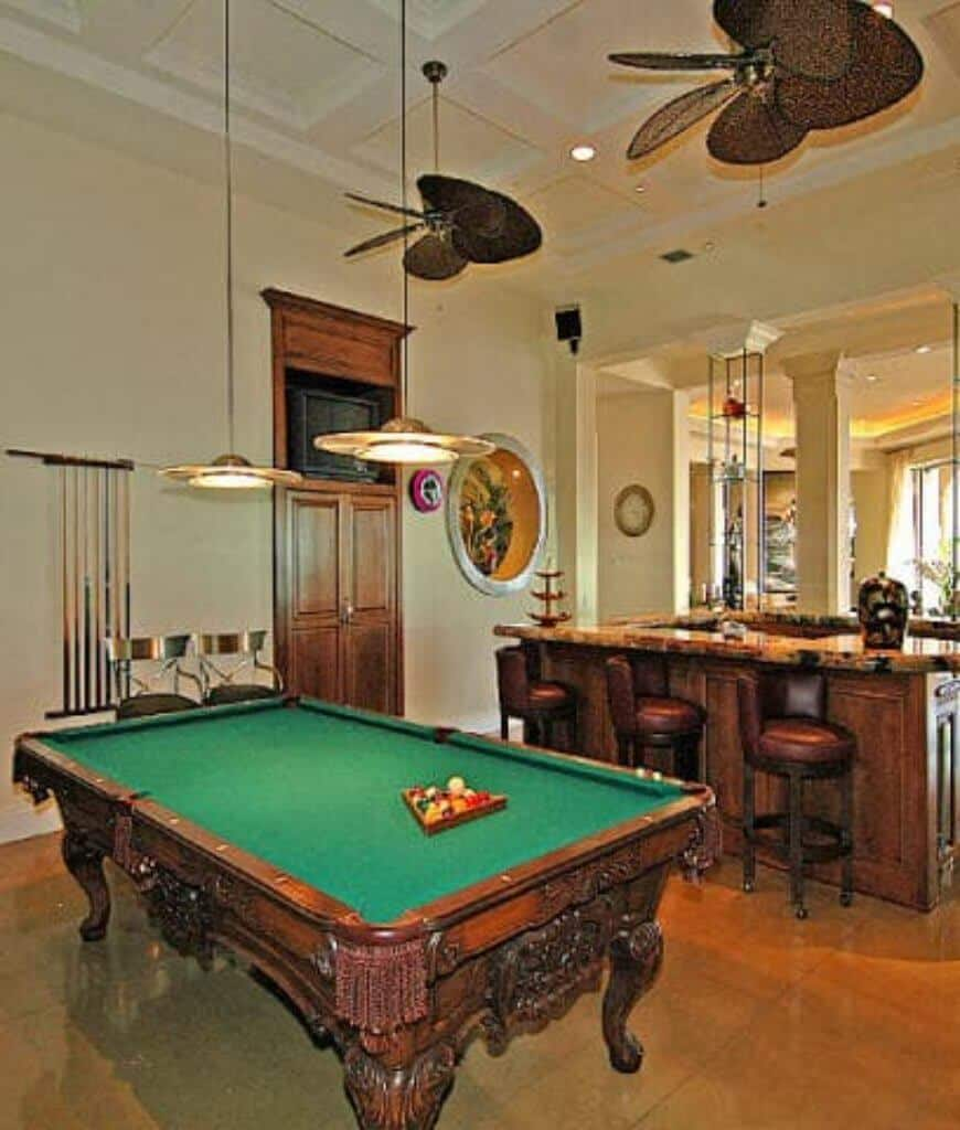 Warm bar area with a small television and carved wood pool table illuminated by round pendants that hung from the coffered ceiling.