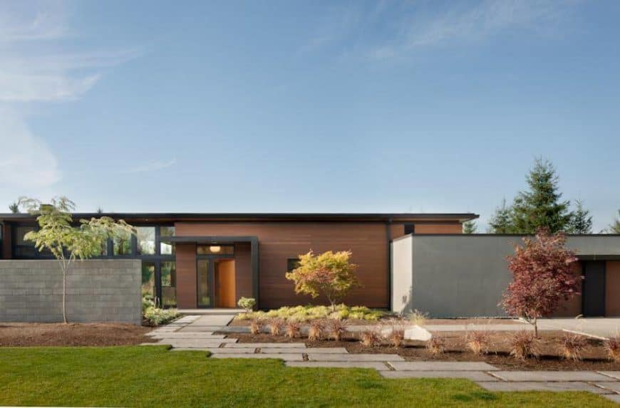 A modern home with a stylish concrete walkway leading the home's garden and lawn area.