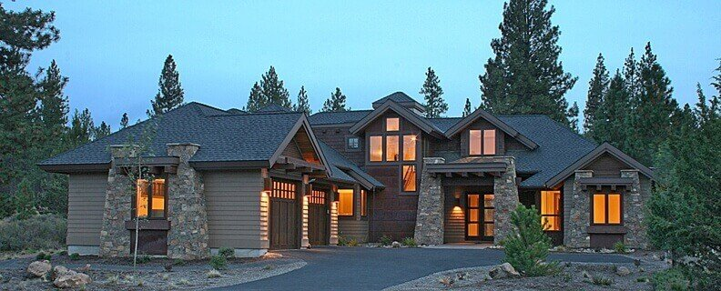 This Craftsman-Style contemporary house has three pairs of stone tapered posts that support the exposed beams of the windows and the main door entryway. The dark roofing is a nice complement to the wooden walls that are illuminated by warm yellow light from the wall-mounted lamps.