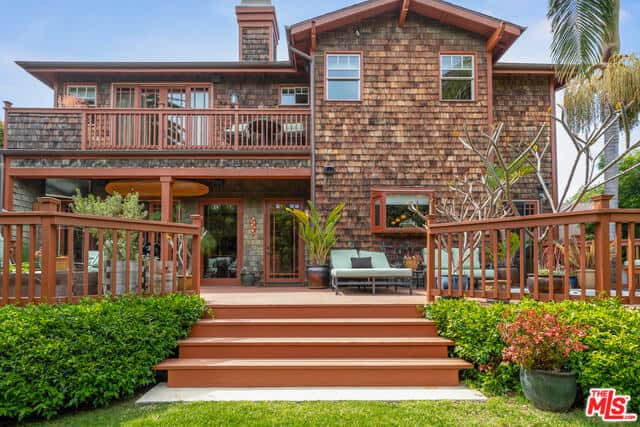 This contemporary Craftsman-Style house exudes a warm and welcoming vibe with its redwood railings, glass doors, and exposed beams of the open gable roof. A lovely second-floor balcony watches over the open spaces of the backyard that is designed for comfort.