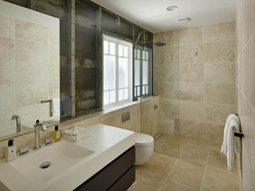 There is uniform brown marble tiles on the flooring and walls of this Cottage-style bathroom brightened by the natural lights coming in from the window. The floating vanity has black modern drawers that contrast the white porcelain sink and the toilet beside it.