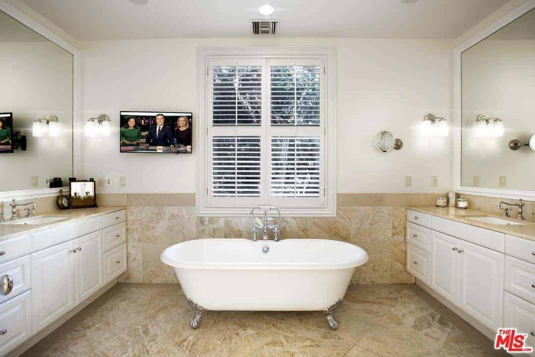 The freestanding bathtub with silver legs stands in the middle of the Cottage-style bathroom right below the shuttered windows. This seats in the middle of the two vanities that are on opposite sides complemented by the brown marble floor and backsplash.