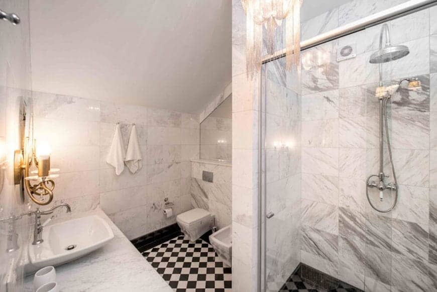 This Cottage-style bathroom has a black and white checkered flooring complemented by the white marble tiles of the walls with streaks of light gray to it. This is also seen in the glass-enclosed shower area across from the vanity.