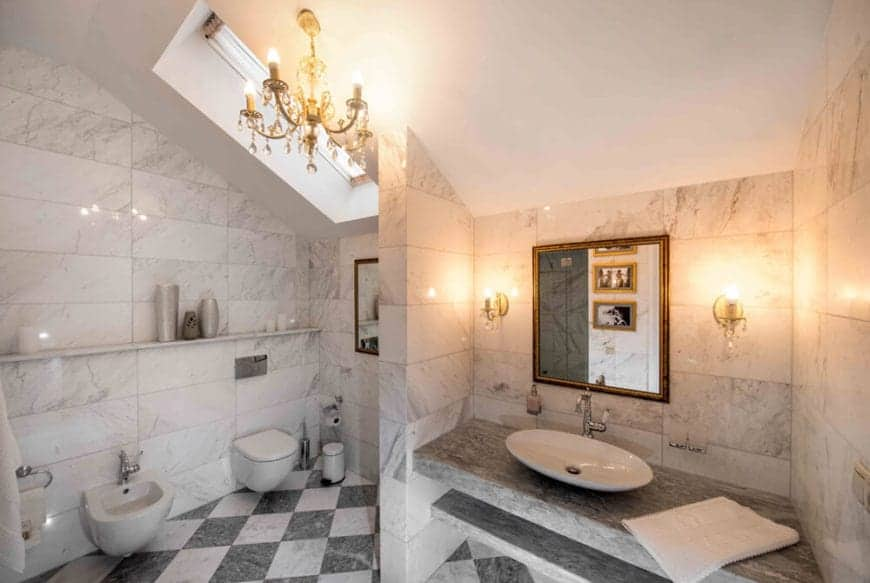 The gray and white marble checkered flooring works quite well with the gray marble countertop that supports the white freestanding sink on top. This setup is complemented by the warm glow of the wall-mounted lamps flanking the mirror.