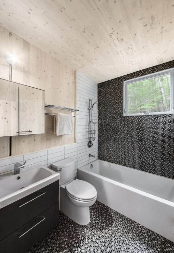 The black modern floating vanity of this Cottage-style bathroom matches well with the mosaic tiles of the flooring. This is also applied onto the wall of the shower area that houses the window above. The wooden ceiling matches with the floating cabinet above the vanity.