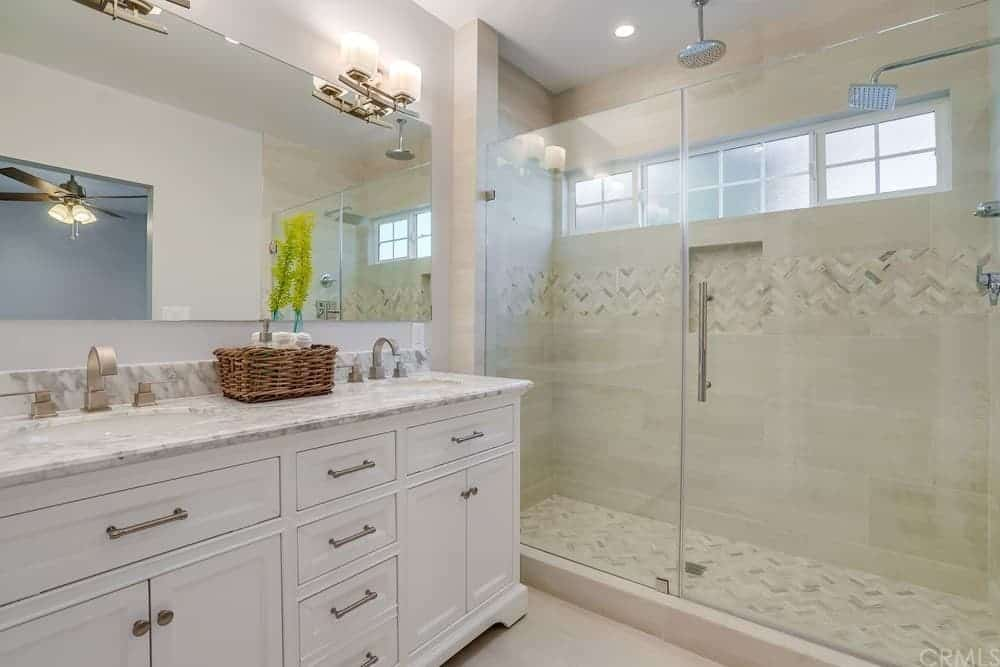 The shower area of this Cottage-style bathroom is separated by the glass wall and glass door from the vanity area that has a white wooden two-sink vanity topped with a large mirror that is illuminated by the wall-mounted lamps.