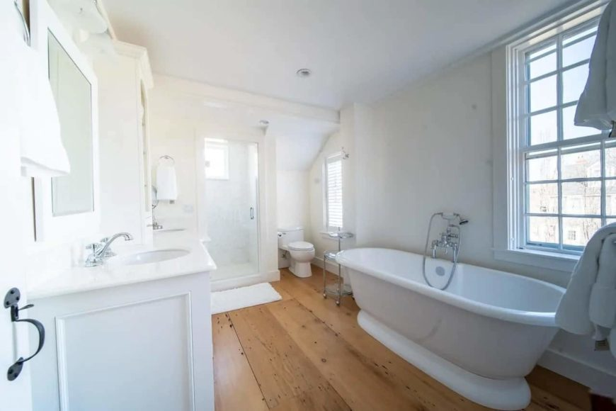 The freestanding porcelain bathtub of this Cottage-style bathroom is placed by the window across from the white wooden vanity. Next to this is the glass door that opens up to the shower area at the far wall.