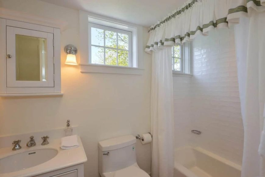 The charming textured white walls of this Cottage-style bathroom is a nice rustic complement to the white porcelain tub, toilet and sink that is topped with a wooden medicine cabinet with a mirror.