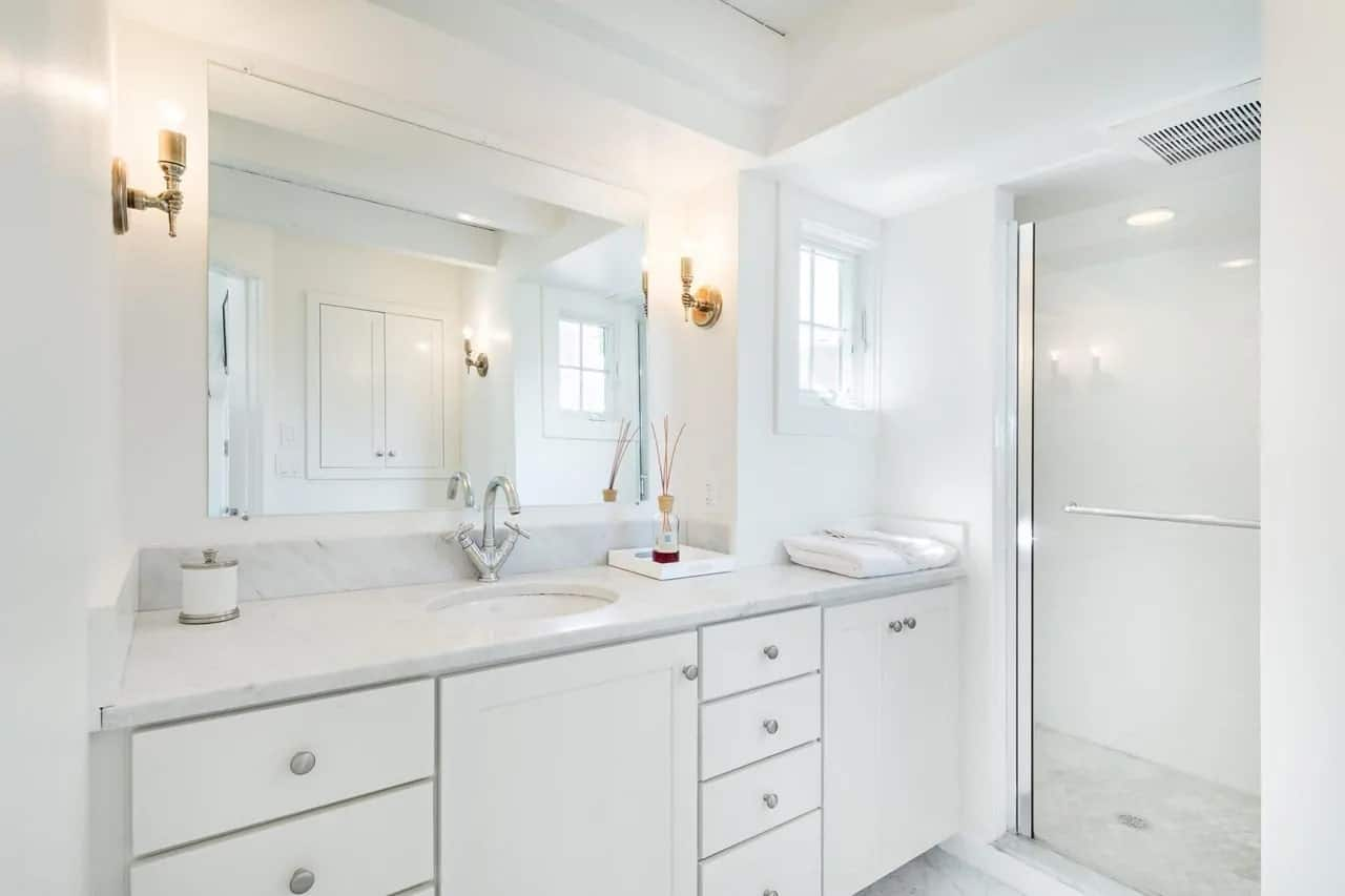 The bright white vanity is complemented by its light gray details along with the stainless steel fixtures. This is then topped with a vanity mirror that is flanked by a couple of decorative wall-mounted brass lamps.