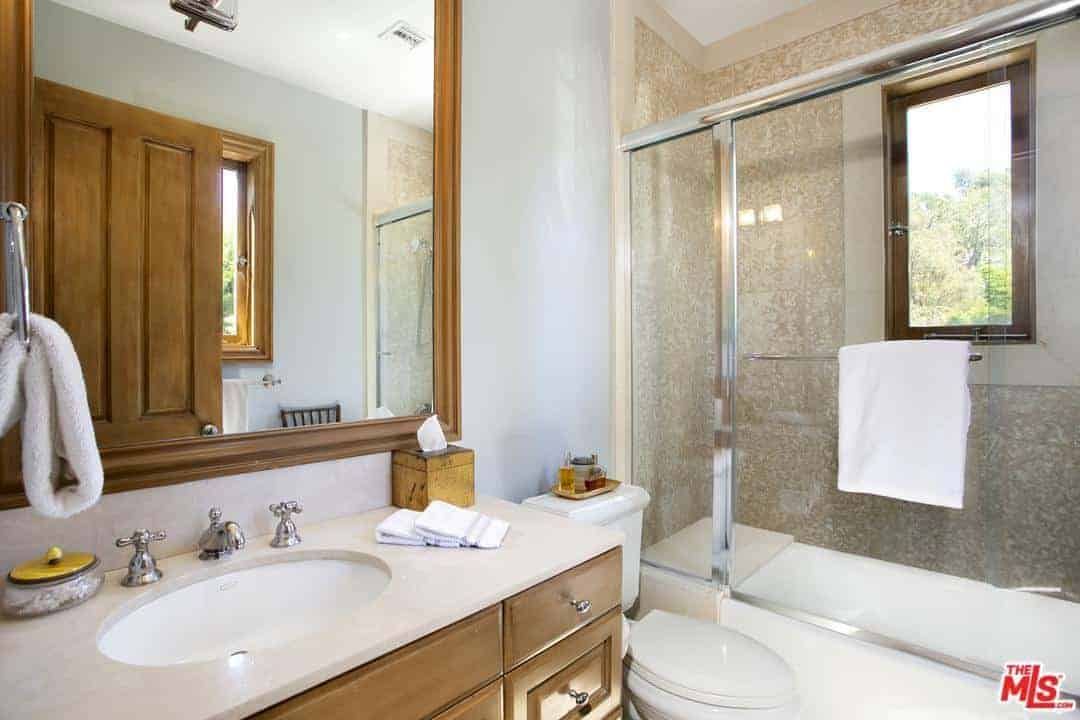 The light gray walls are complemented by the charming wooden cabinets and drawers of the vanity that pairs well with the frame of the wall-mounted mirror. Beside this is the toilet that matches well with the white bathtub that also serves as the flooring for the shower area.