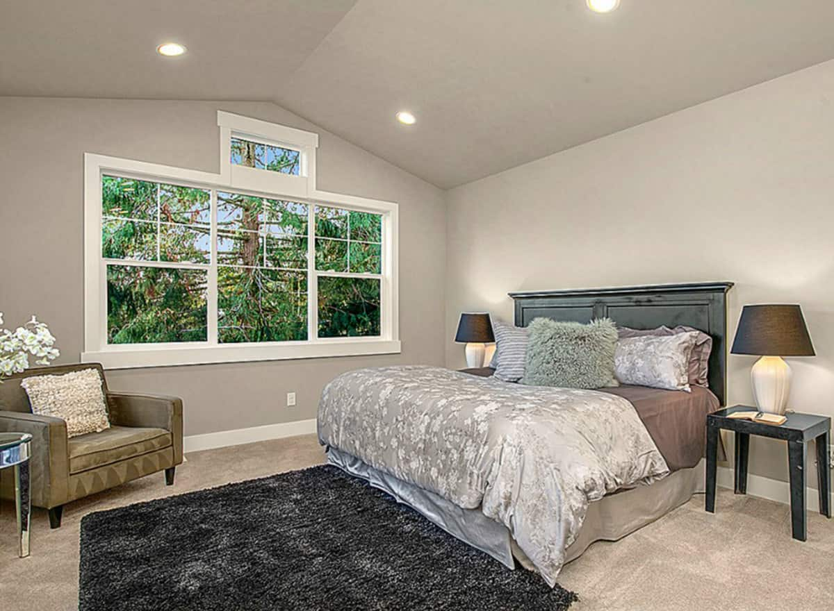 This spacious bathroom has gray walls, gray cathedral ceiling and gray carpeted flooring that is contrasted by the black wood headboard, bedside table and the area rug at the foot of the bed.