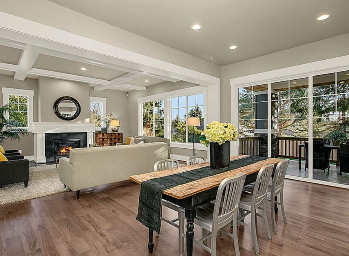 This is an informal dining area beside the living room. It has a simple wood-top dining table paired with modern steel chairs that stand out against the hardwood flooring.