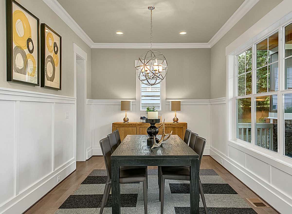 This is a formal dining room with a dark wooden dining table surrounded by matching black chairs that contrast the bright and elegant wainscoting that matches the moldings and the window frame.