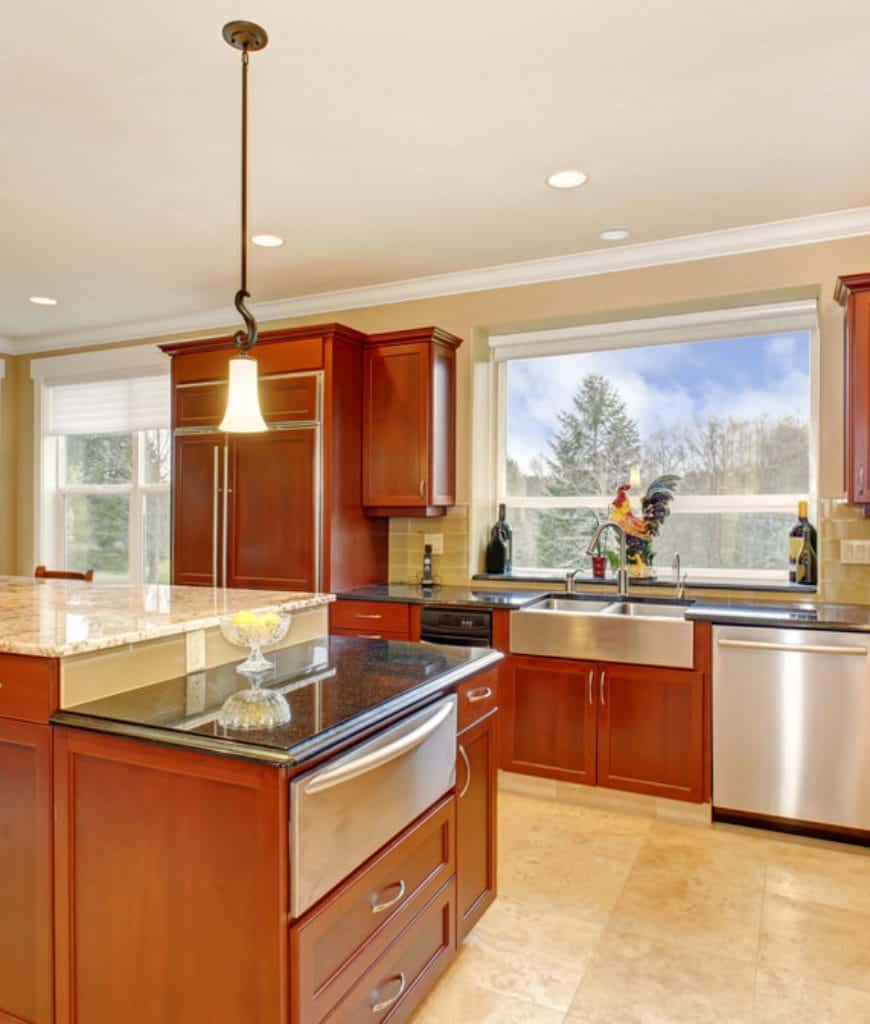 The marble floor and kitchen island countertop are contradicted by the redwood drawers and cabinets that are built-in to the walls. Silver appliances are paired with silver handles that stand out against the redwood background. An eclectic touch is brought by a rooster standing behind the modern sink and faucet.