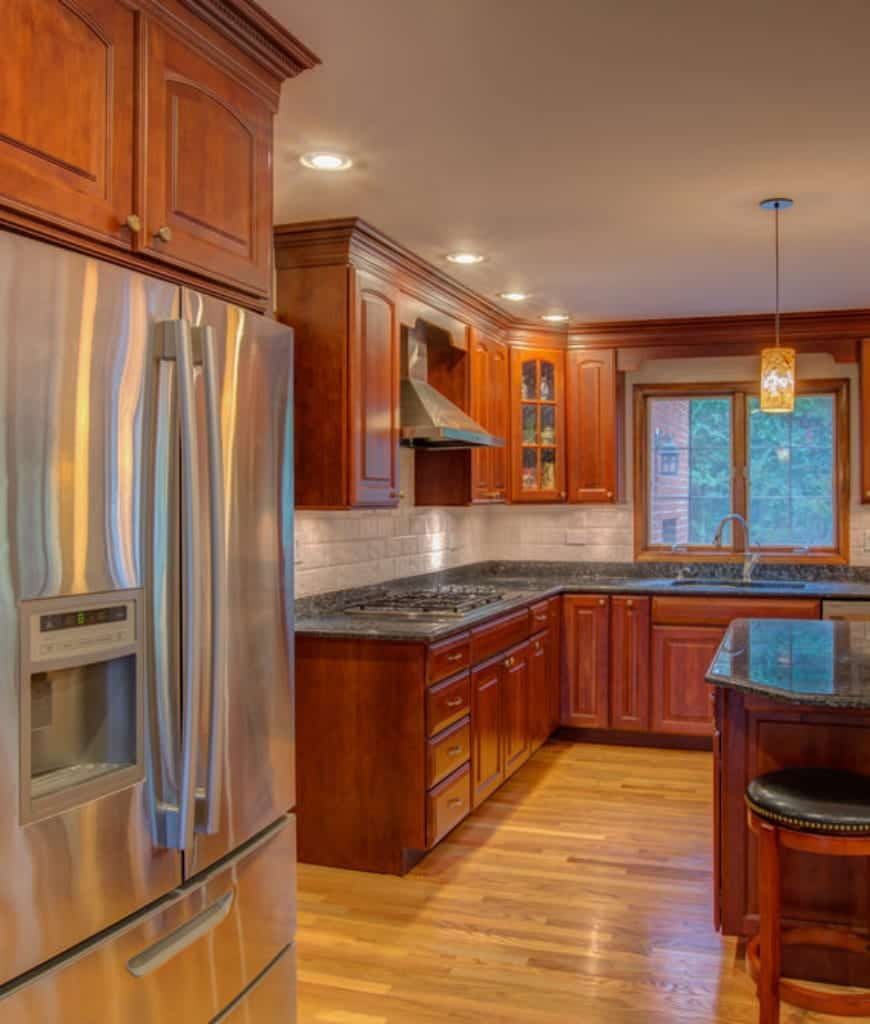 Hardwood floors are illuminated with warm yellow light from the quaint pendant light hanging from the white ceiling. This light is properly reflected in the surfaces of the dark island and peninsula countertops. Redwood hues are applied onto the cabinets and drawers.