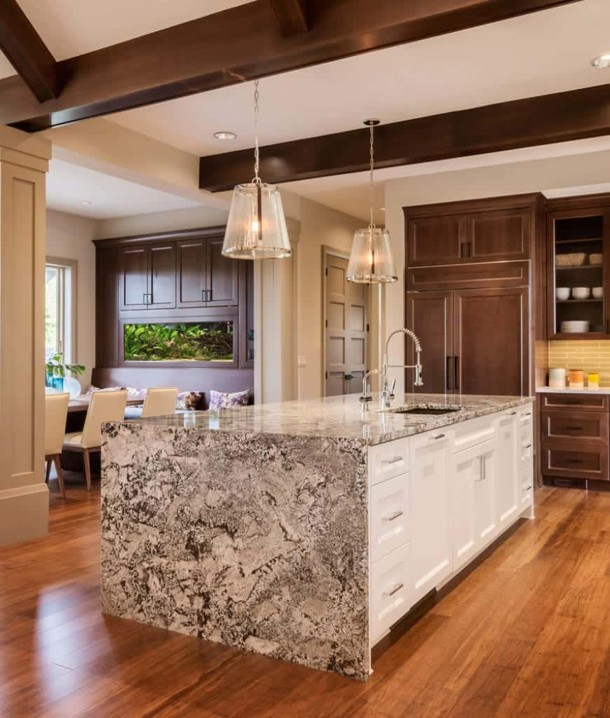 Elegance and sophistication exude from this kitchen with its crystal pendants lights, wooden cabinets, and massive kitchen island counter with a patterned countertop. This is enhanced by the lovely wooden exposed beams that work well with the redwood flooring.