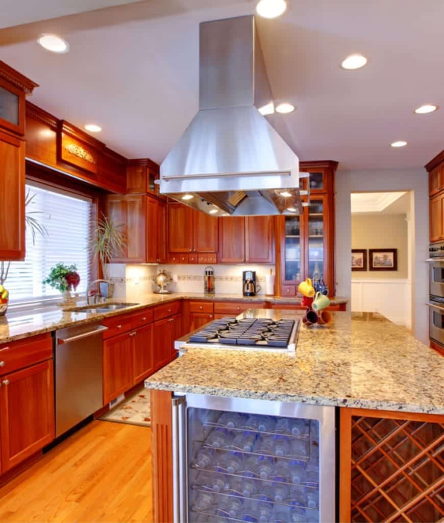 Sleek and modern appliances built-into this Craftsman-Style kitchen balances out the traditional wooden elements of the floor,  and mounted cabinets that follow the lay of the ceiling and forms a charming wooden alcove over the faucet area.