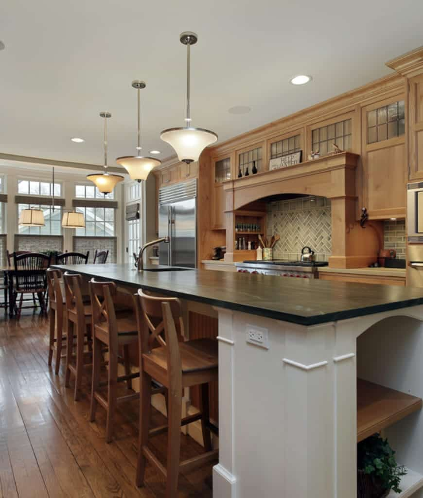 Brilliant hanging pendant lamps are mounted over the central kitchen island with a dark stone countertop and wooden stools. The massive woodwork of this Craftsman-Style kitchen extends from the fridge and stove to the oven and fitted with cabinets and drawers.