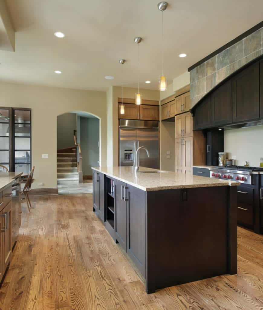 The wooden cabinets and drawers in this Craftsman-Style kitchen are painted with a dark hue that contrasts with the bright white ceiling pin lights and hanging pendant lights over the kitchen island. Hardwood flooring with emphasized wooden lines gives depth and warmth.