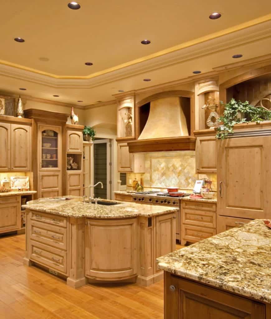The natural wooden hues and beige tray ceiling give this kitchen an air of traditional warmth. This is augmented by the various warm lighting that illuminates the marble countertops and the lovely patterned backsplash of the stove area.