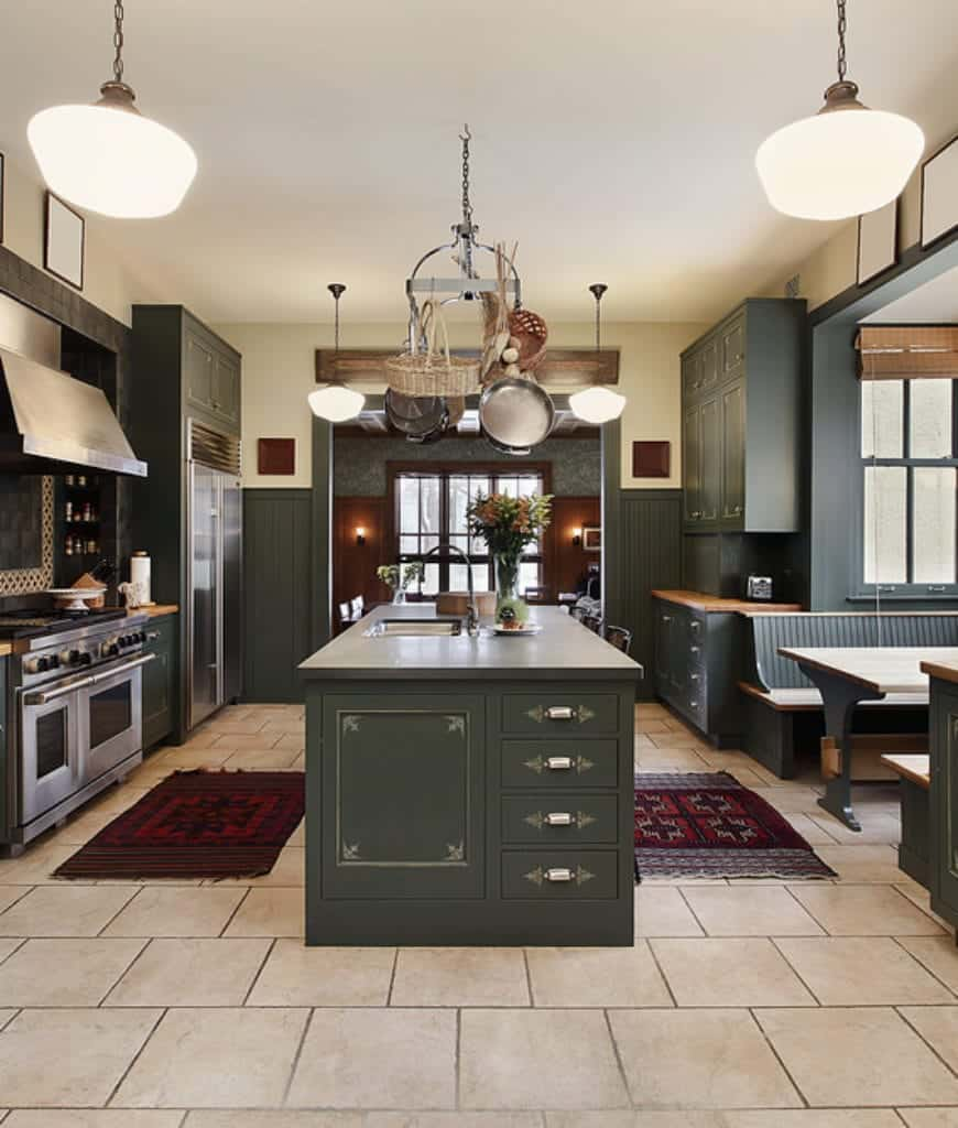 Medium-sized pendant lights hang from the four corners of the white ceiling illuminating the deep green hue of the wooden built-in cabinets and drawers as well as the kitchen island and fridge housing. The white-tiled flooring serves as a background to the vibrant colors of the patterned area rugs.