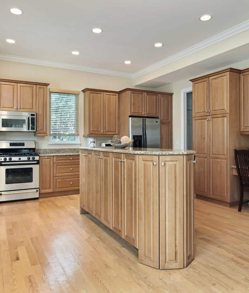 The kitchen island in the middle of the hardwood floor has a charming design and fitted with multiple cabinets that follow its shape. The wooden hues and cabinet handles are consistent with the hanging cabinets and drawers that surround the kitchen area.