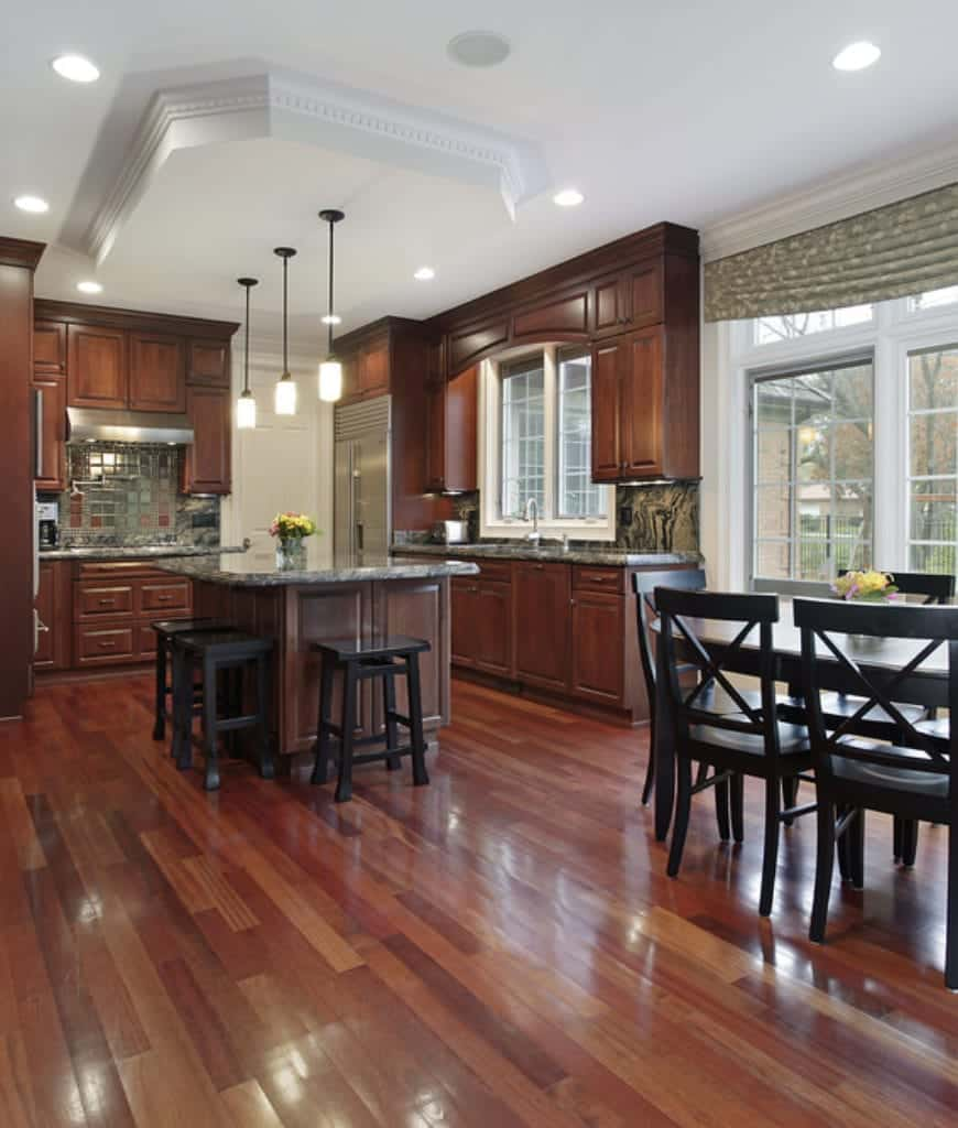 A brilliant wooden structure with molding protrudes from the white ceiling that holds the three pendant lights over the kitchen central island made of redwood that is reflected onto the kitchen peninsula. These redwood drawers and cabinets seem to blend into the redwood floor that goes well with the dark stools.