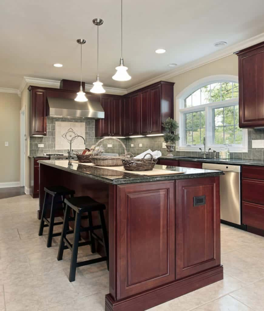 The built-in hanging cabinets, kitchen peninsula with drawers and the central kitchen island are given a redwood material and elegant tray finish. These wooden structures pop out against the light hues of the beige walls and white-tiled floor. These are balanced by the green-tinged countertops and backsplash.