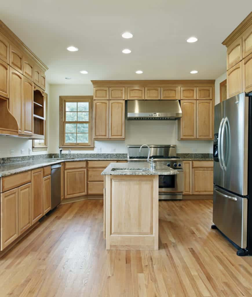 The modern metallic appliances of this Craftsman-Style kitchen bring a modern touch to this traditional kitchen that is dominated with wooden hues. The hardwood floor coincides with the wooden cabinets of the kitchen peninsula and hanging cabinets. A sense of vibrancy is brought by the marble countertops and backsplash against the white walls.
