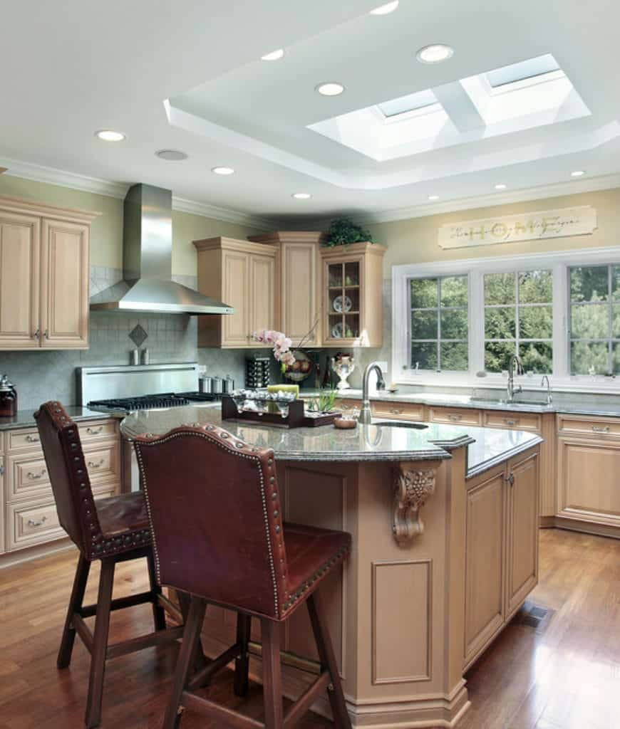 The bright and airy quality of this kitchen is largely due to the white tray ceiling that has sunroofs bringing in natural light that augments the pin lights lining the edges of the ceiling and the French windows. This bright quality illuminates the wooden cabinetry of the kitchen island and peninsula as well as the hardwood flooring.